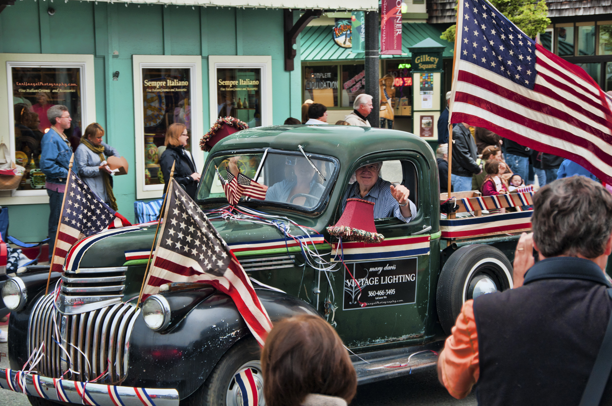 old couple driving green antique car with American flags