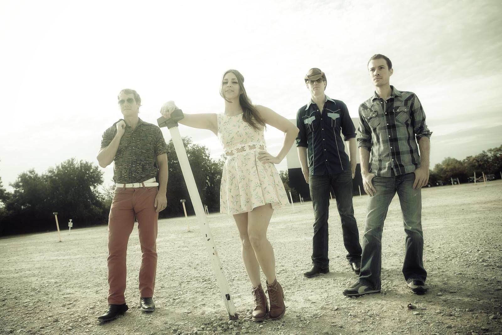 4 members of Angela Perley & The Howlin' Moons standing in field