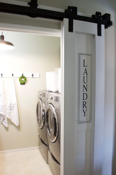 A barn door painted white makes a stylish door for a laundry room.