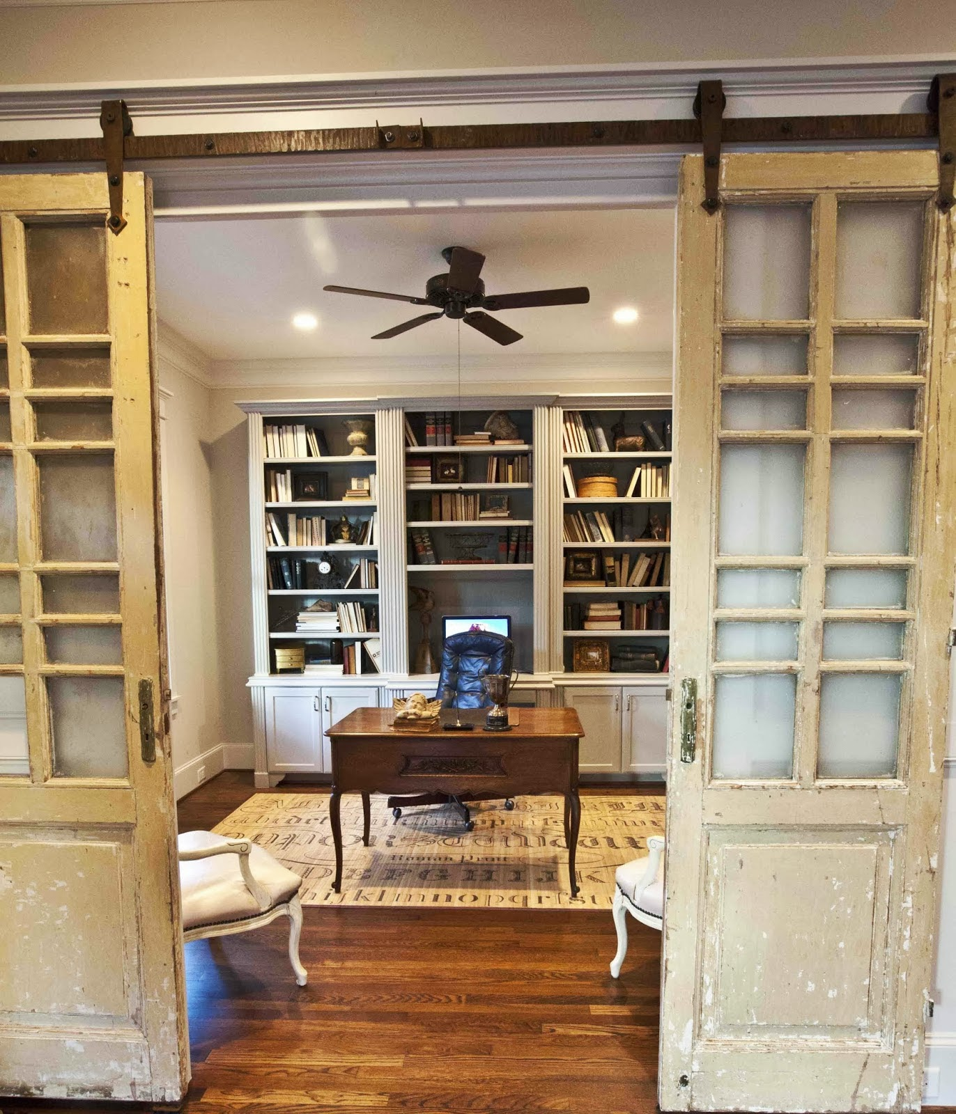 Distressed barn doors slide away to reveal a beautiful study with wood floors and a small, antique looking desk.