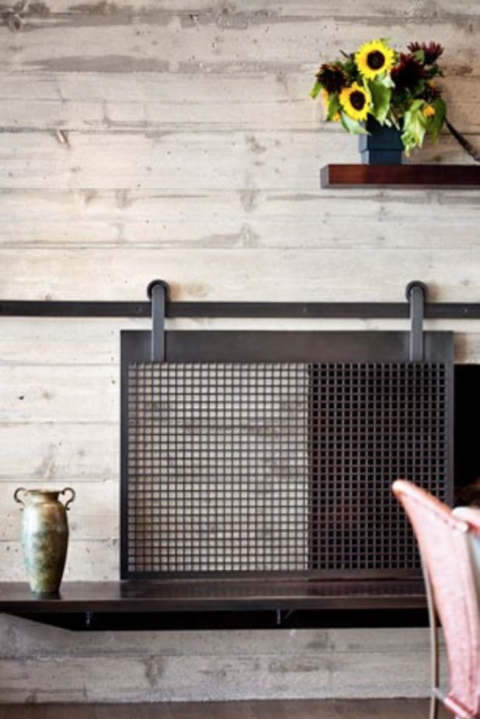 A white stone fireplace with an elegant but rustic looking wire grating slid in from of it.