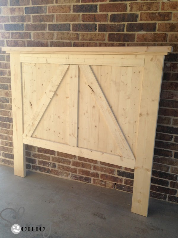 A partially completed DIY barn door headboard leans against a brick wall.