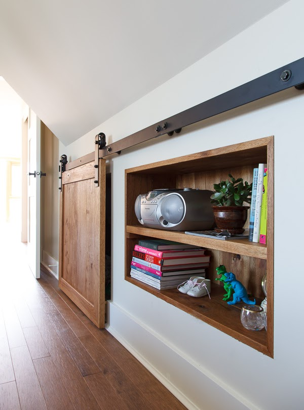 In a bedroom with wood floors and white walls, a simple sliding barn door hides a storage area.