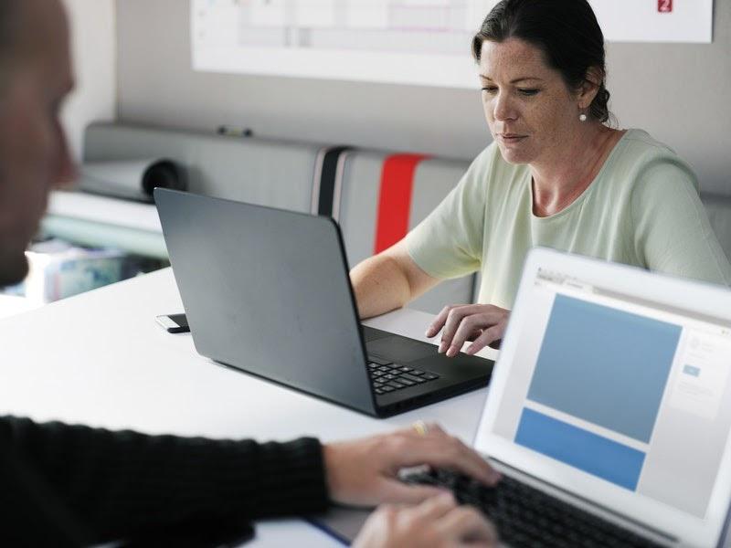 man and woman looking at laptops