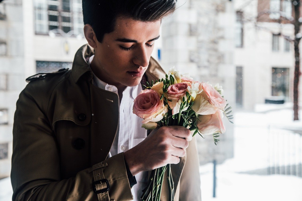 A man in a leather jacket sniffs a bouquet of pink flowers.