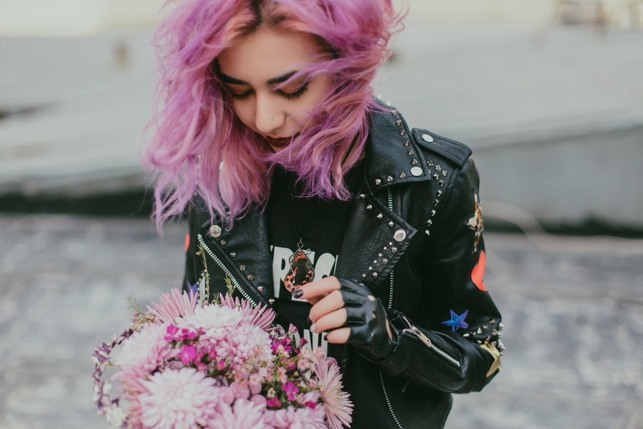 A girl with dyed pink hair looks at the purple flower arrangement in her hands.