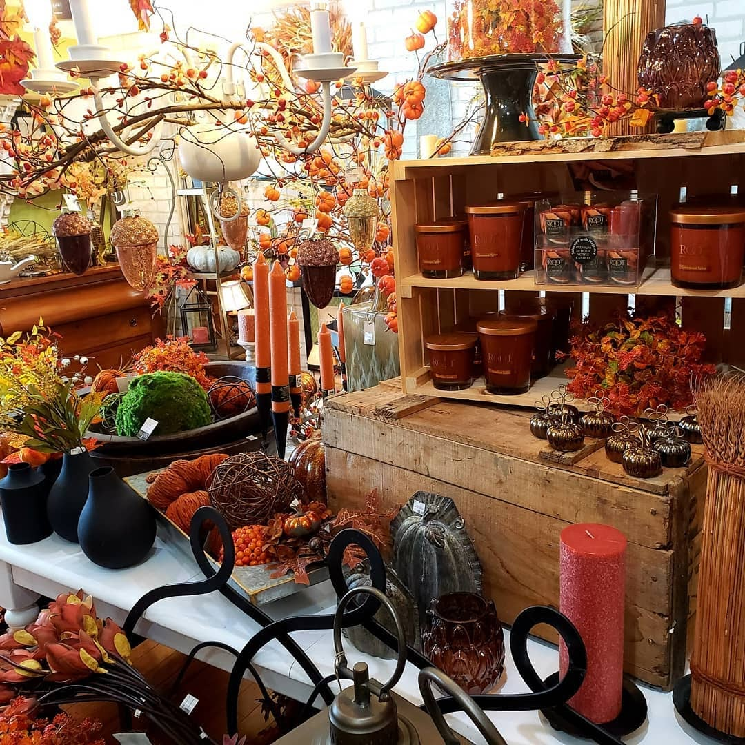 A shelf in Fireplace Gifts And Florist with candles, brass pumpkins, and other kinds of fall decorations.