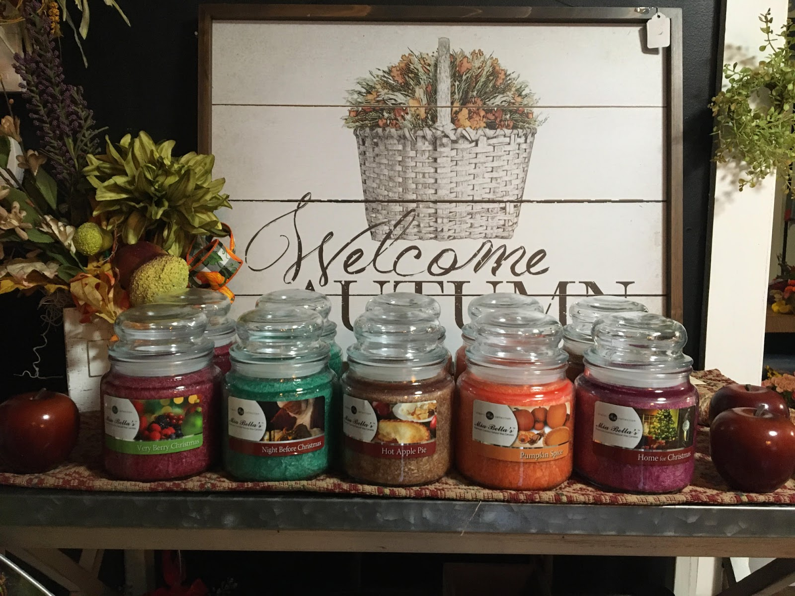 Closeup of a welcome to autumn sign at The Flower Pot. In front of it are five kinds of scented candles.