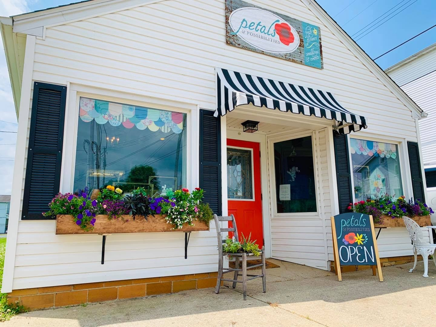 A picture of the Petal and Possibilities storefront. Building is white with flower boxes on windows.