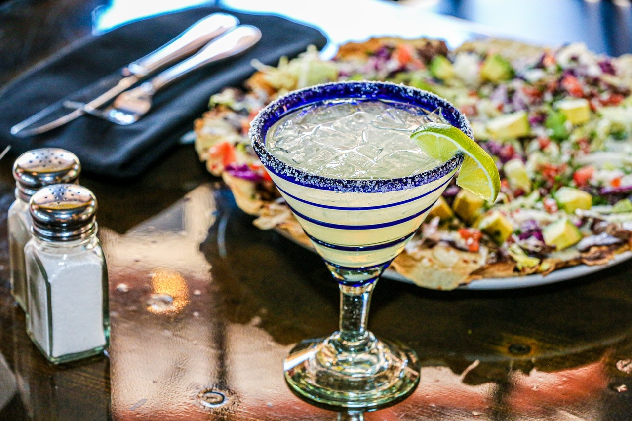 A closeup of a green margarita with salt and a lime on the rim. Behind it is a plate of loaded nachos..