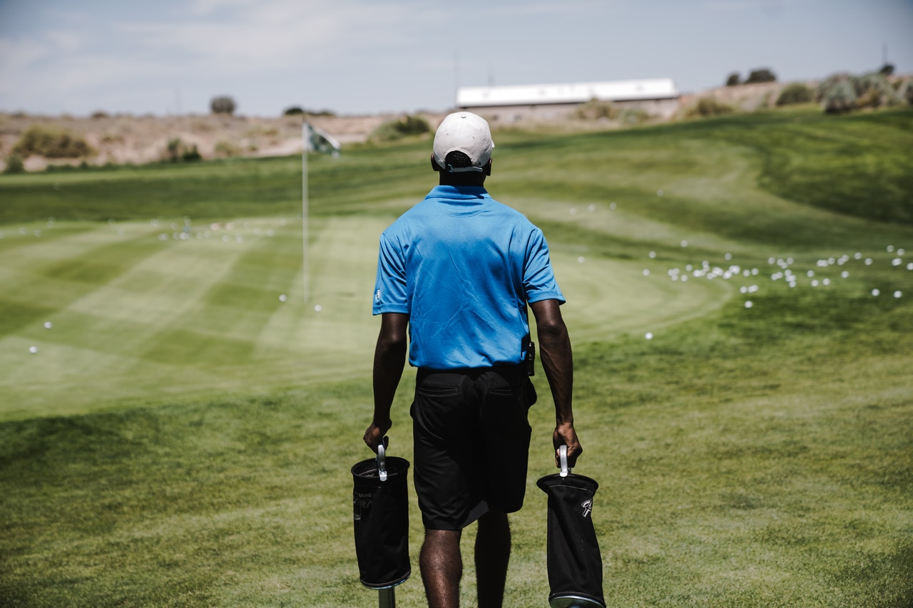 A man in a blue shirt walks on a golf course with two bags of golf clubs in hand.
