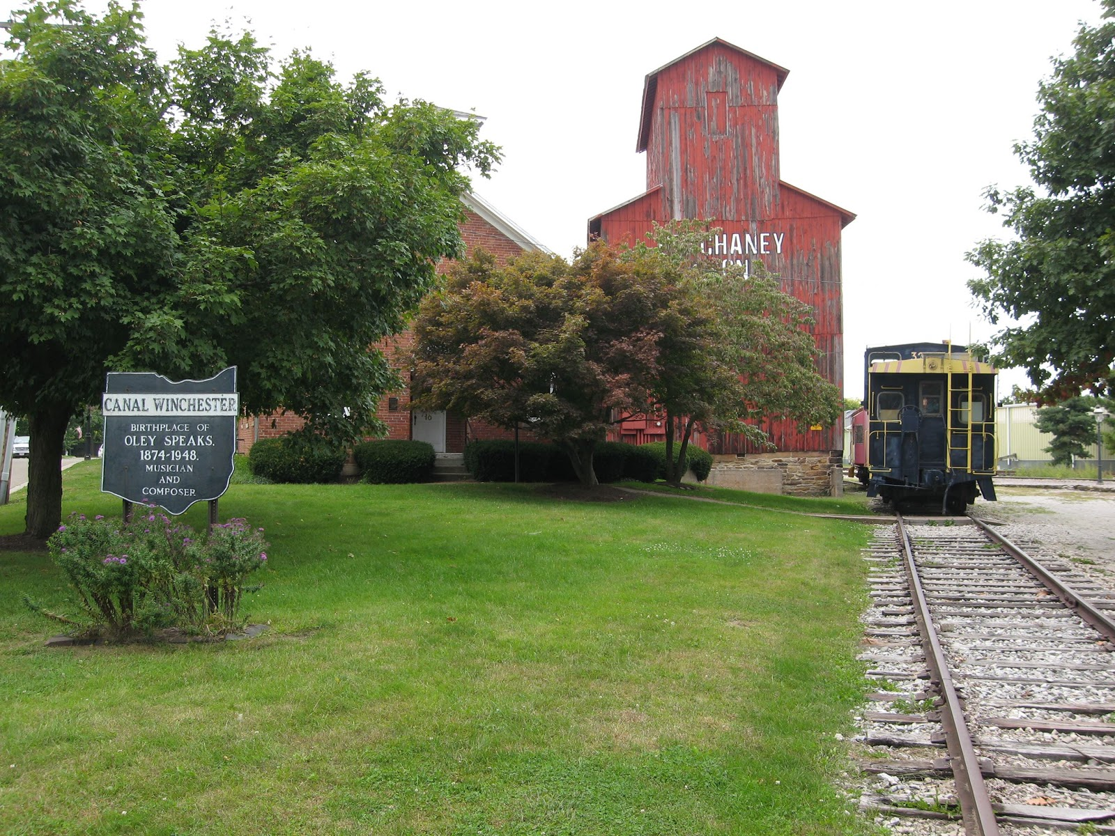 A sign for Canal Winchester, Ohio in front of an old barn and train tracks.