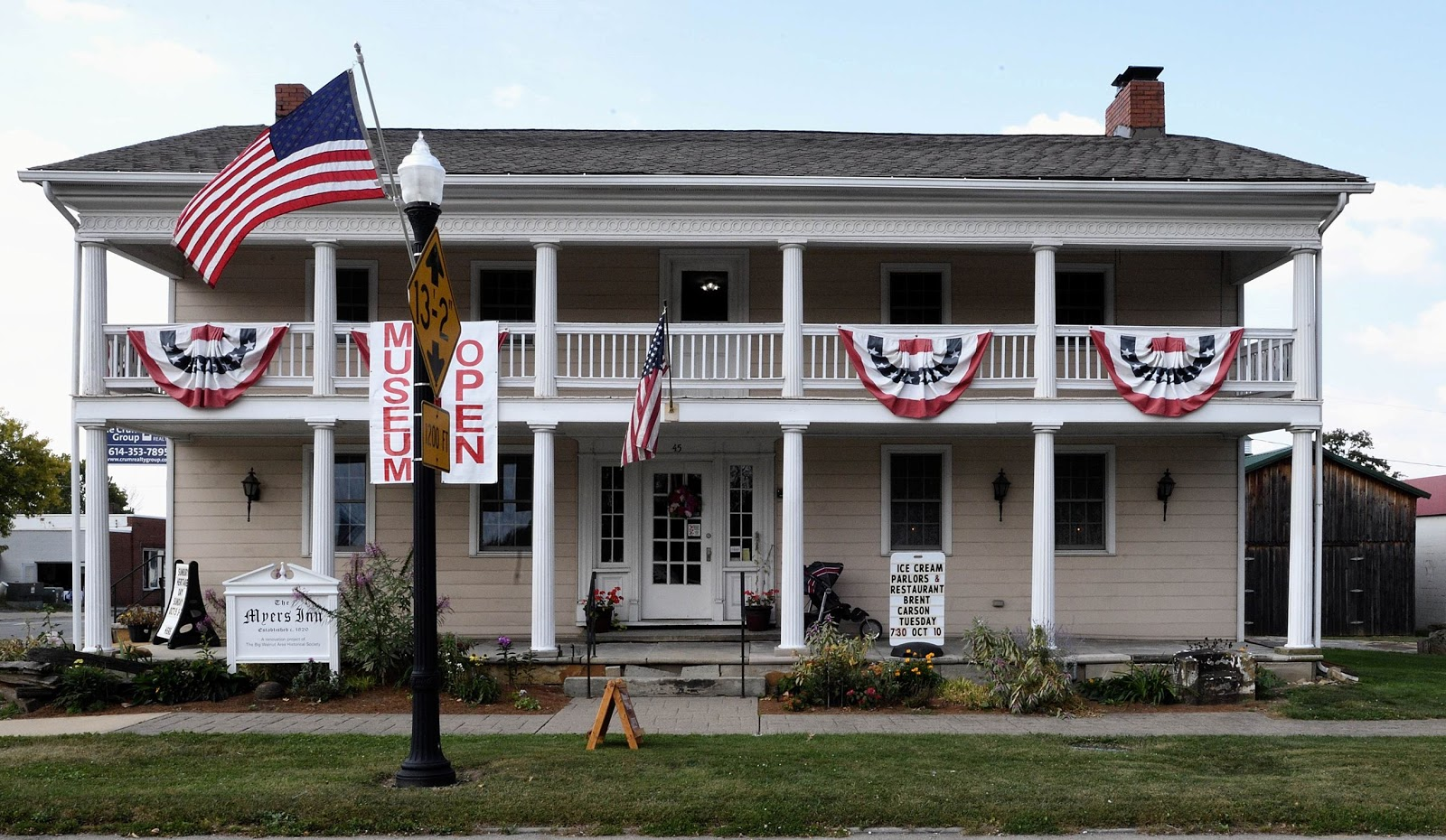 A picture of a historic building with white columns and American flags in Sunbury, Ohio.