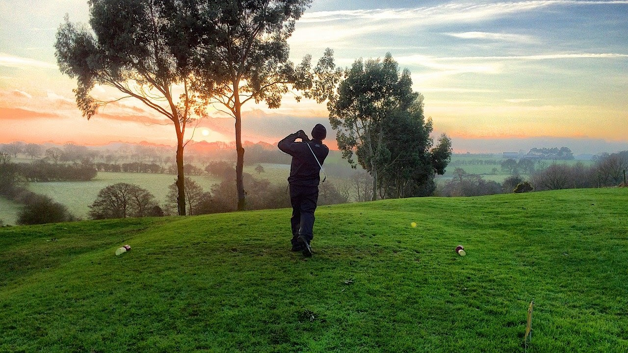 A man swings his club on a golf course as the sun sets.