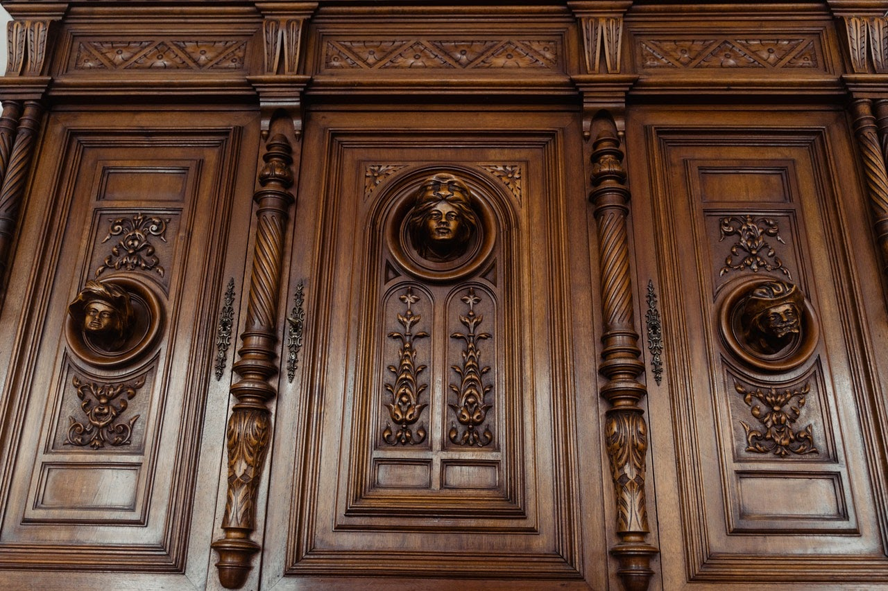 A large turned wood dresser with faces carved into the doors.