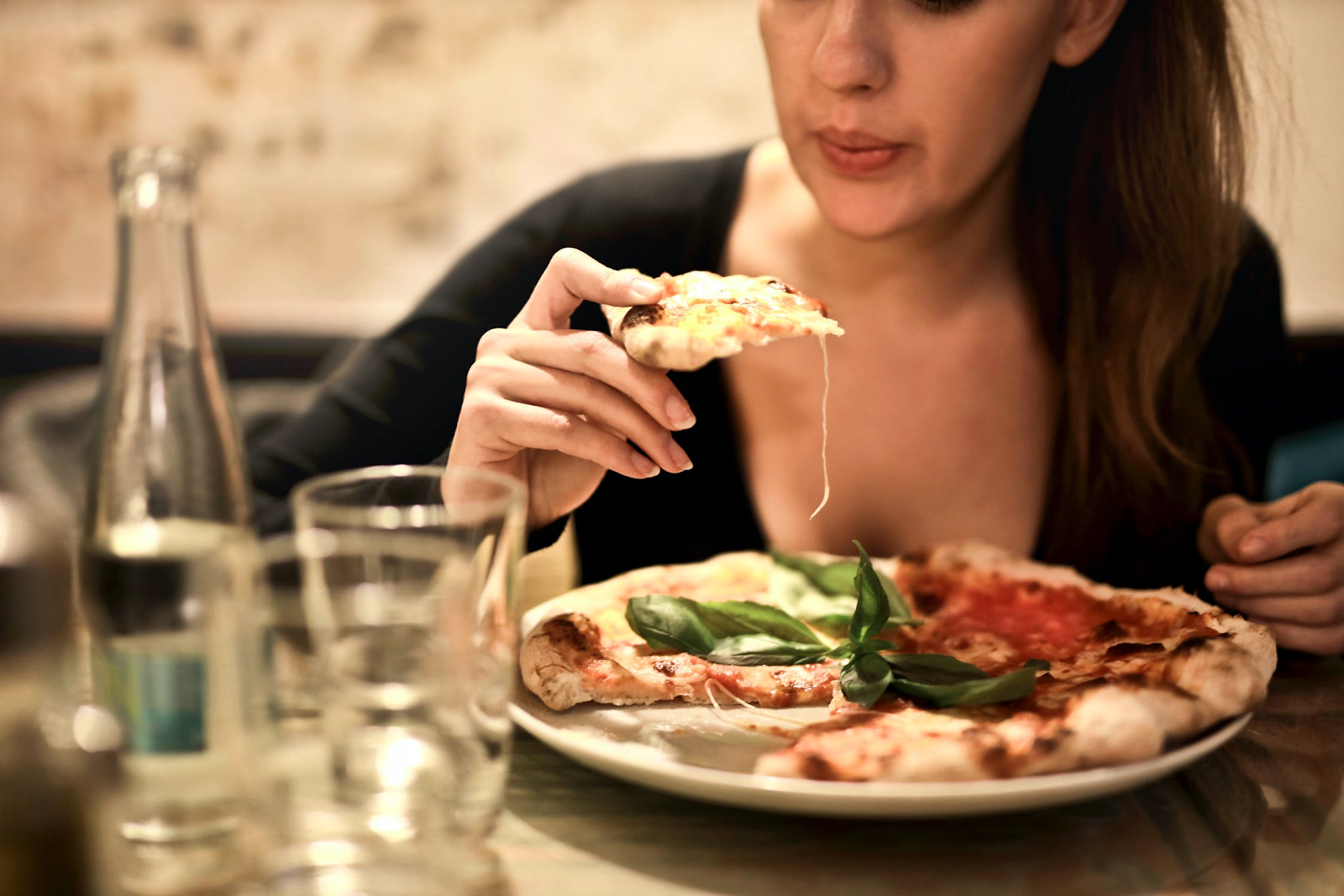 A conclusory image showing a woman enjoying a warm slice of pizza.