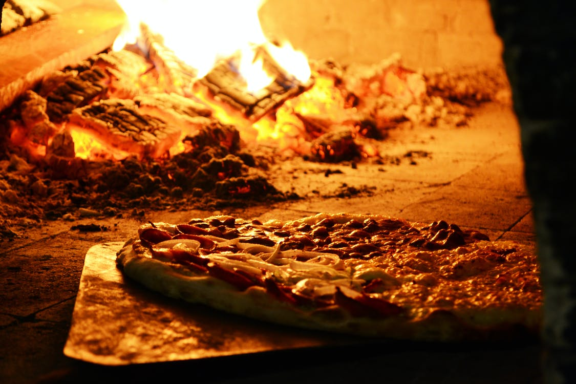 An image of pizza being cooked with a 'family-style' feel as you can find at Marsella's pizza.