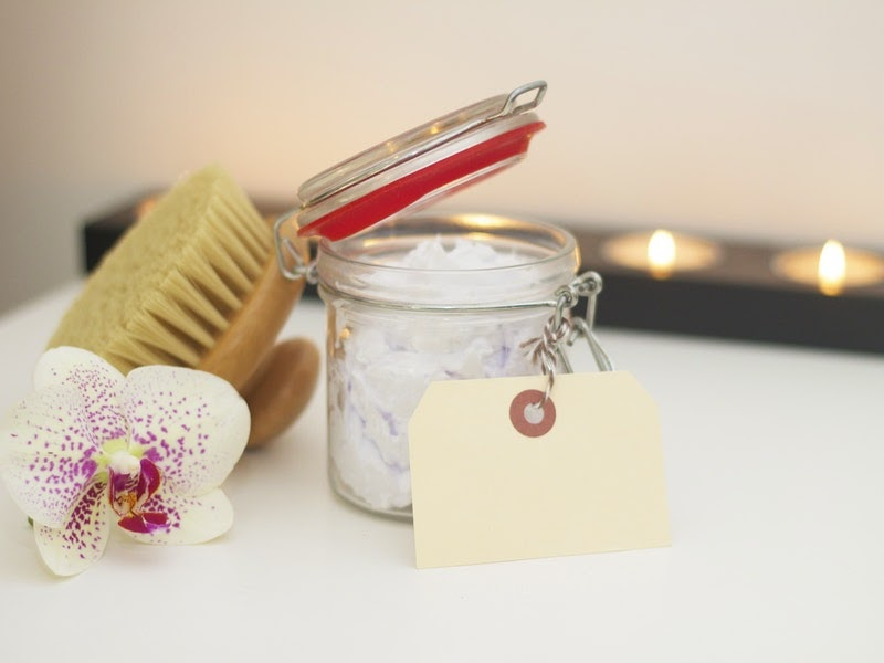 body scrub, a brush, and candles