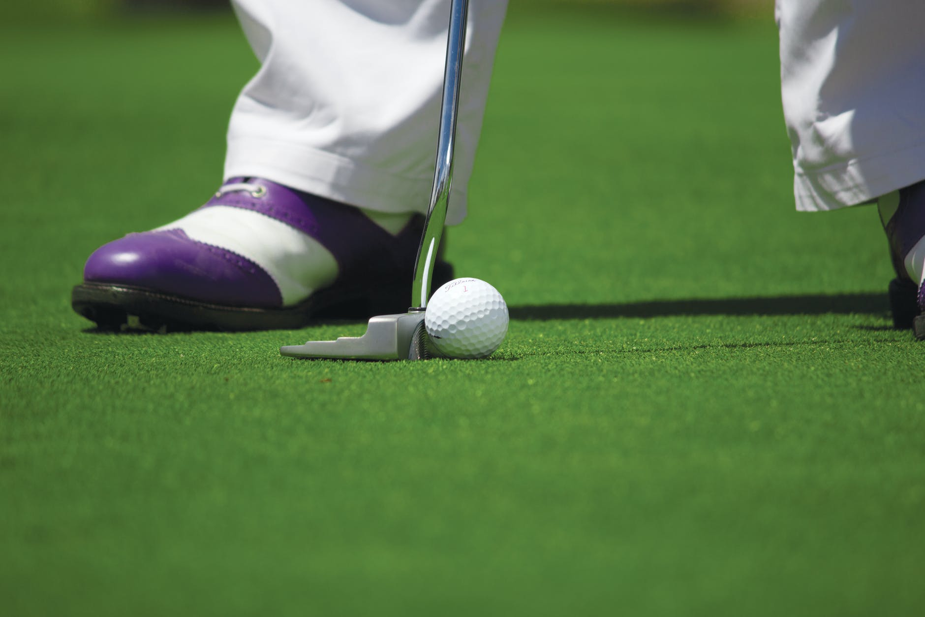 A close up of someone putting on a golf green. They have on purple and white golf shoes and white pants.