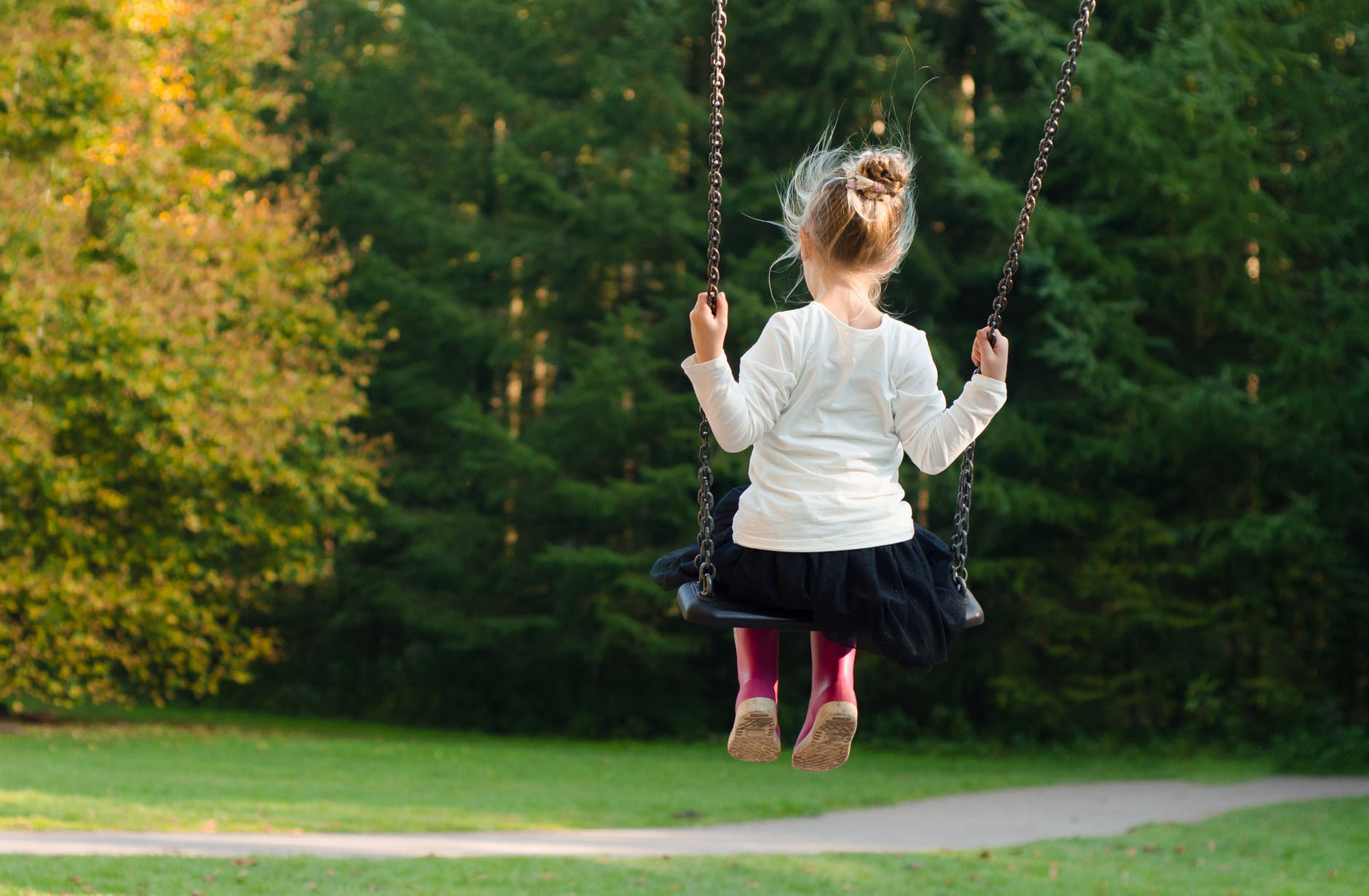 A little girl is swinging on a swing set in a park looking towards the trees.