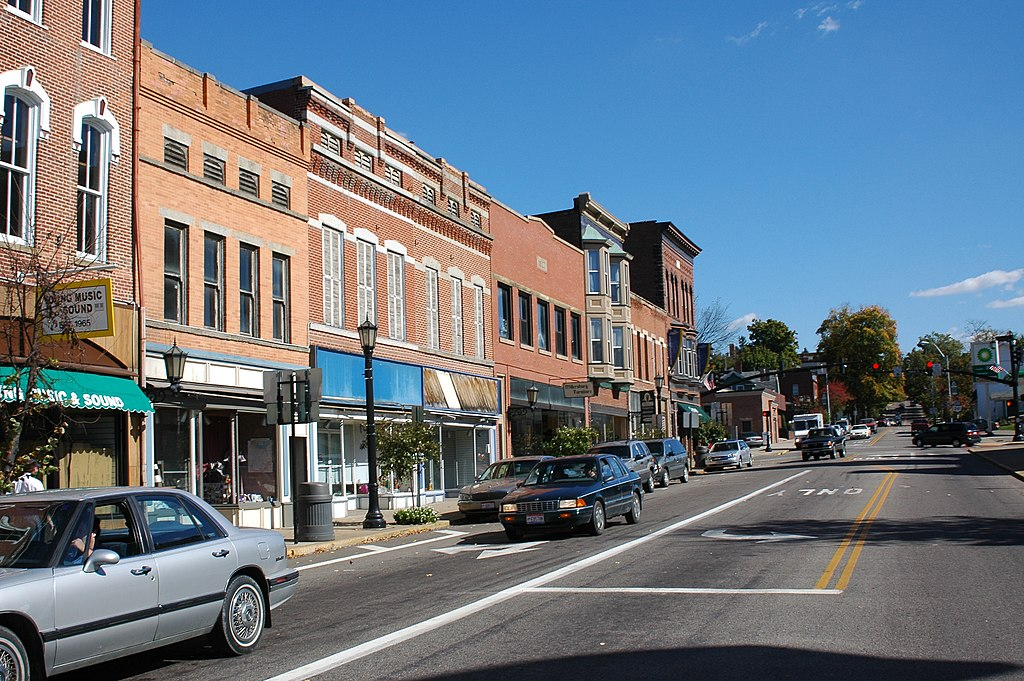 The image shows a downtown area with many storefronts and cars parked along side the road.