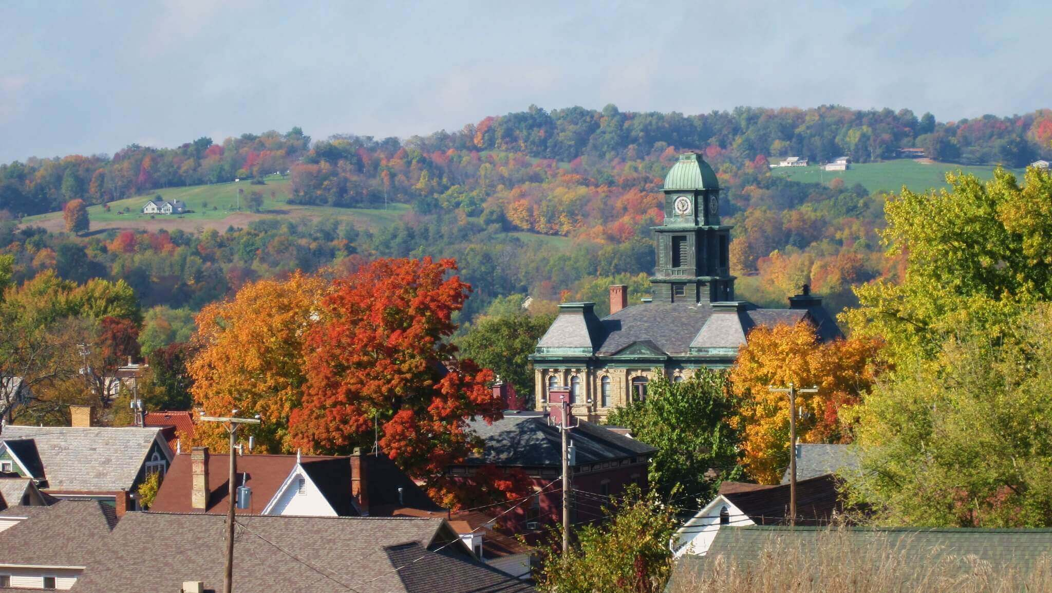 The tops of houses in front of a much taller building with a steeple and a clock. The leaves on the trees are changing color for fall. In the background there are hills and farmland.