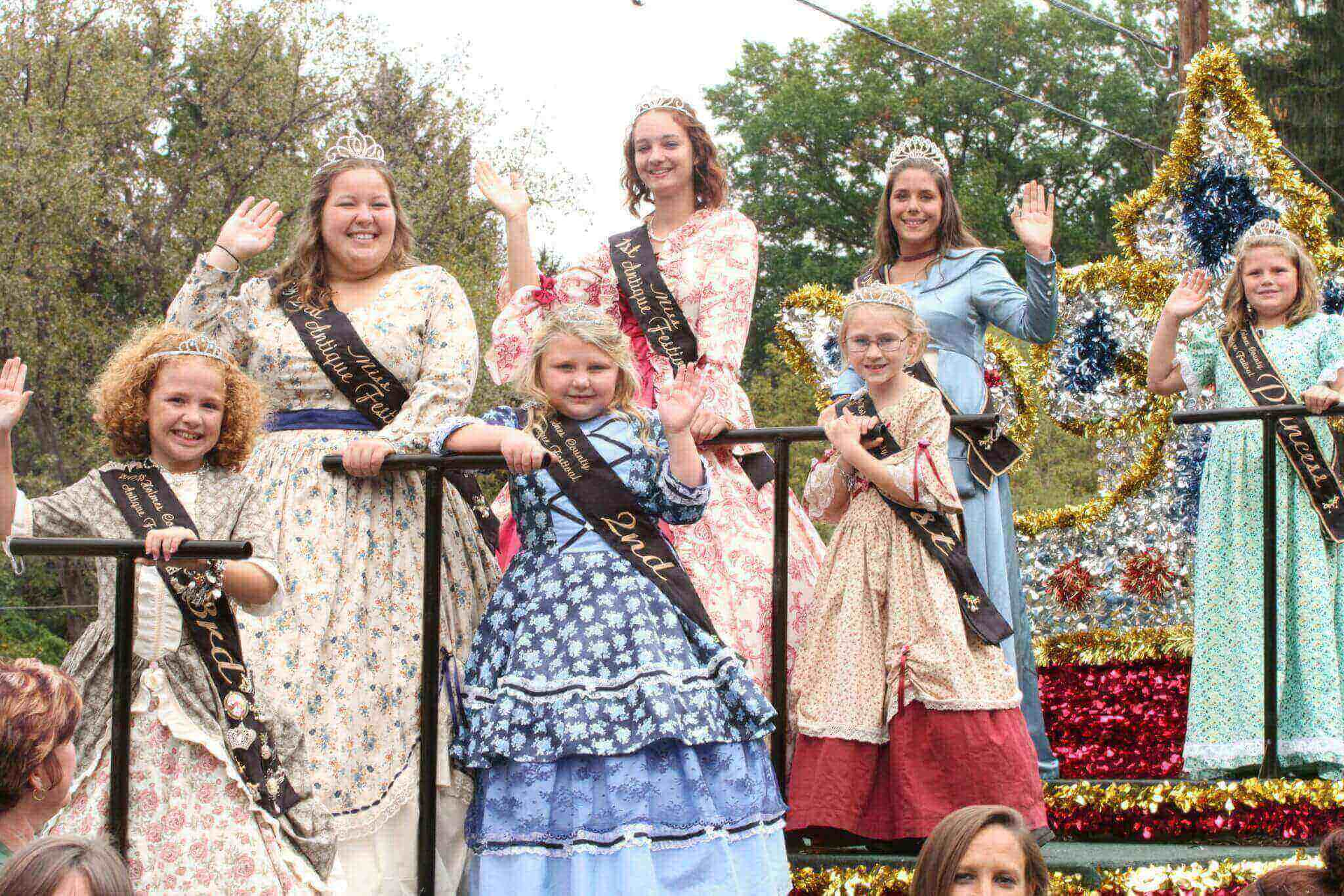 Seven girls stand and wave on a float in a parade. They are all wearing vintage dresses with sashes indicating what place they won in a contest.