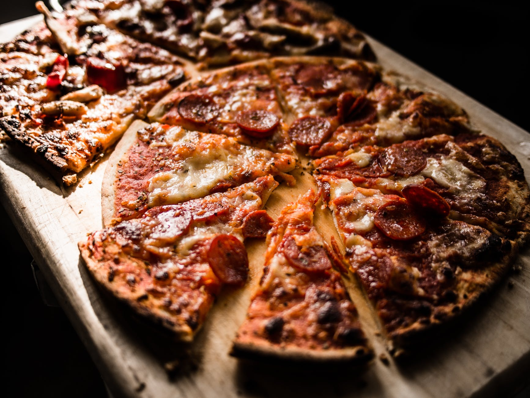Two pepperoni pizzas on a wooden plate