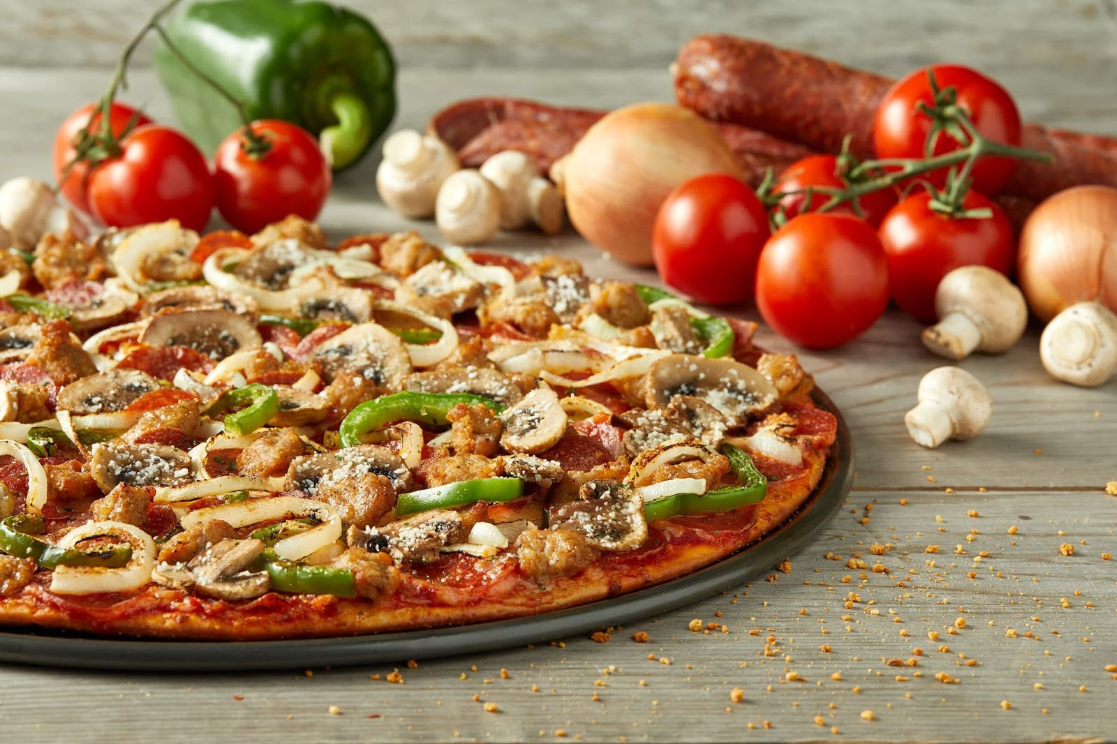 Thin crust mushroom green pepper and onion pizza with tomatoes, mushrooms, onions, green pepper, and sausage in the background