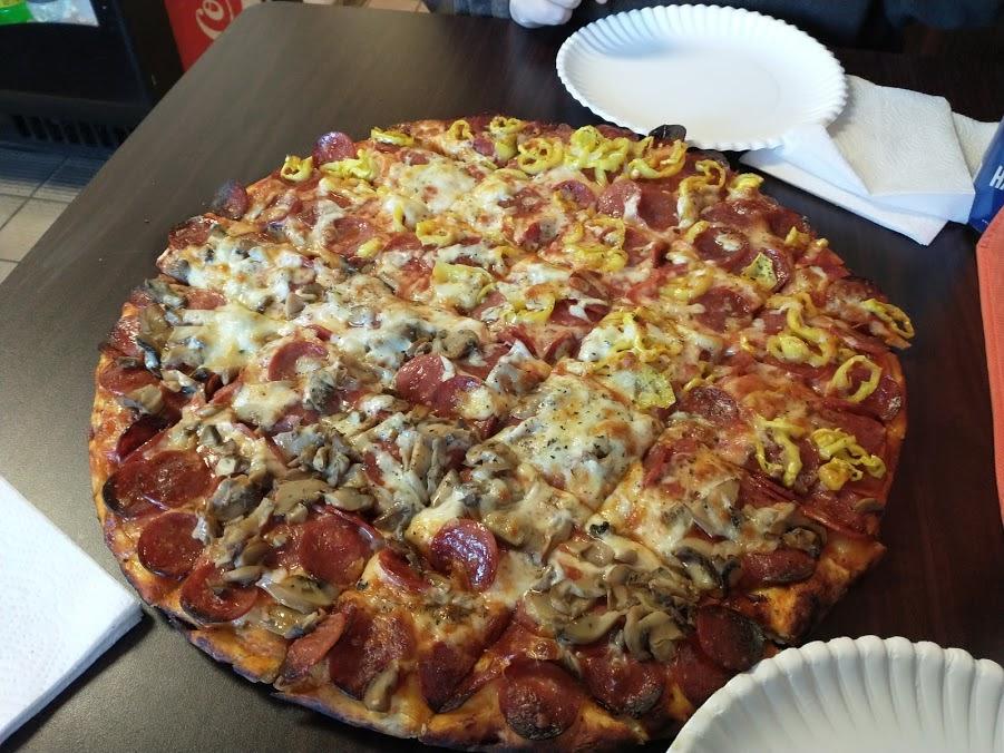 half mushroom, half banana pepper, full pepperoni pizza on a brown table