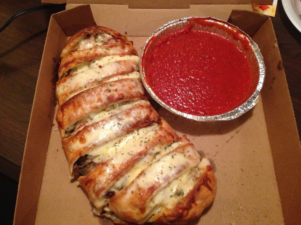 a cheesy stromboli and pie tin of red sauce in a cardboard pizza box