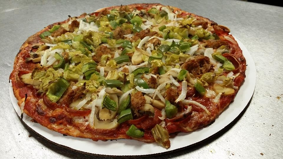 Pizza loaded with onions, green peppers, mushroom, sausage, and pepperoni plus pepperoncini. On a white table.