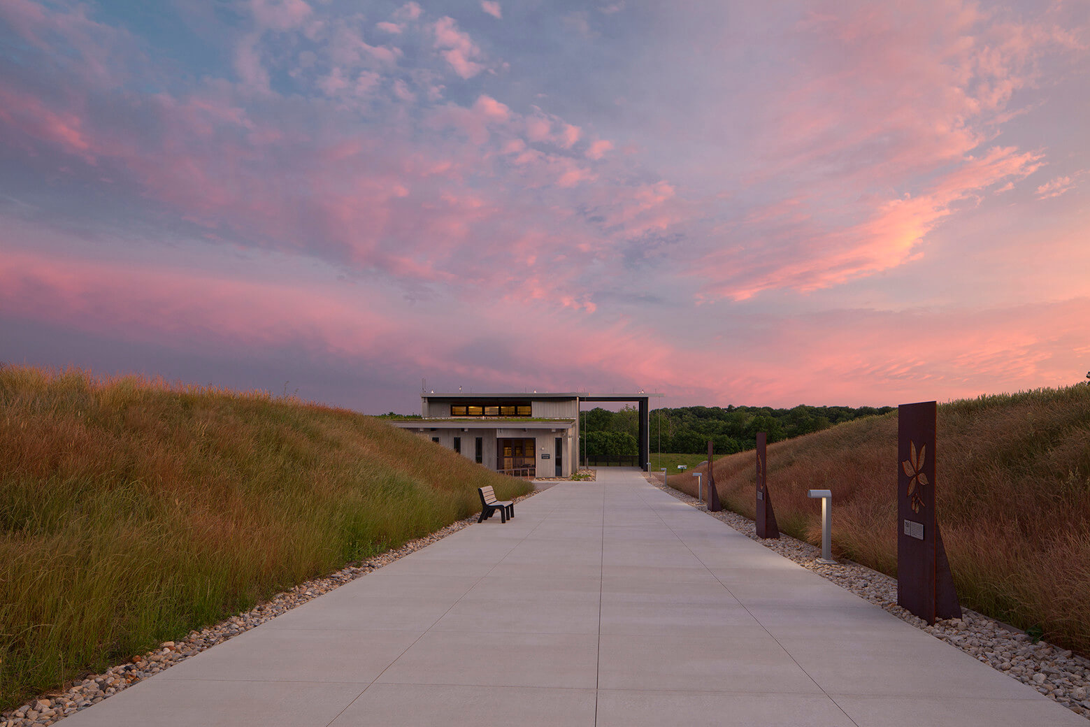 A paved path leads towards a modern building. The path is lined by small grassy hills. The sun is setting, leaving the sky and clouds a faint pink color.