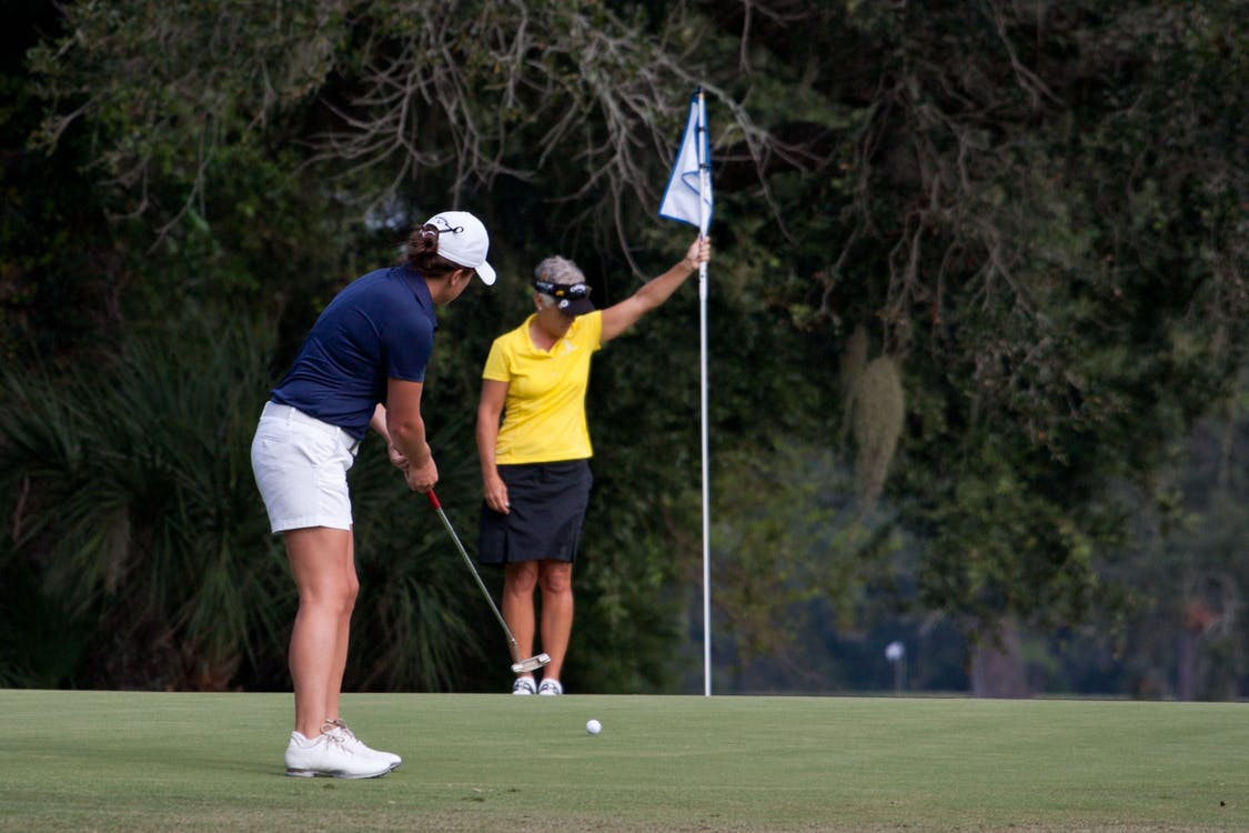 Two women are on a putting green. One is putting, the other holds the flag near the hole.
