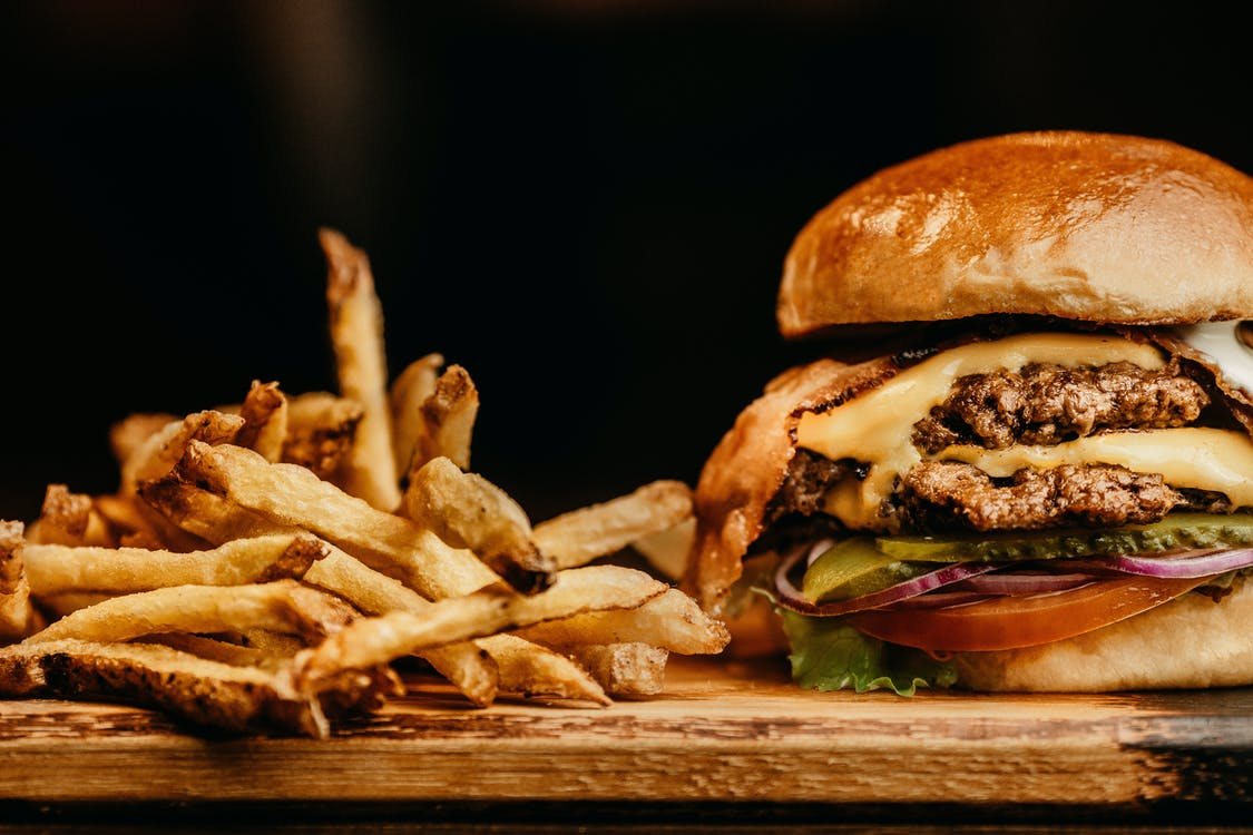 A burger and fries are set on a wooden serving tray.