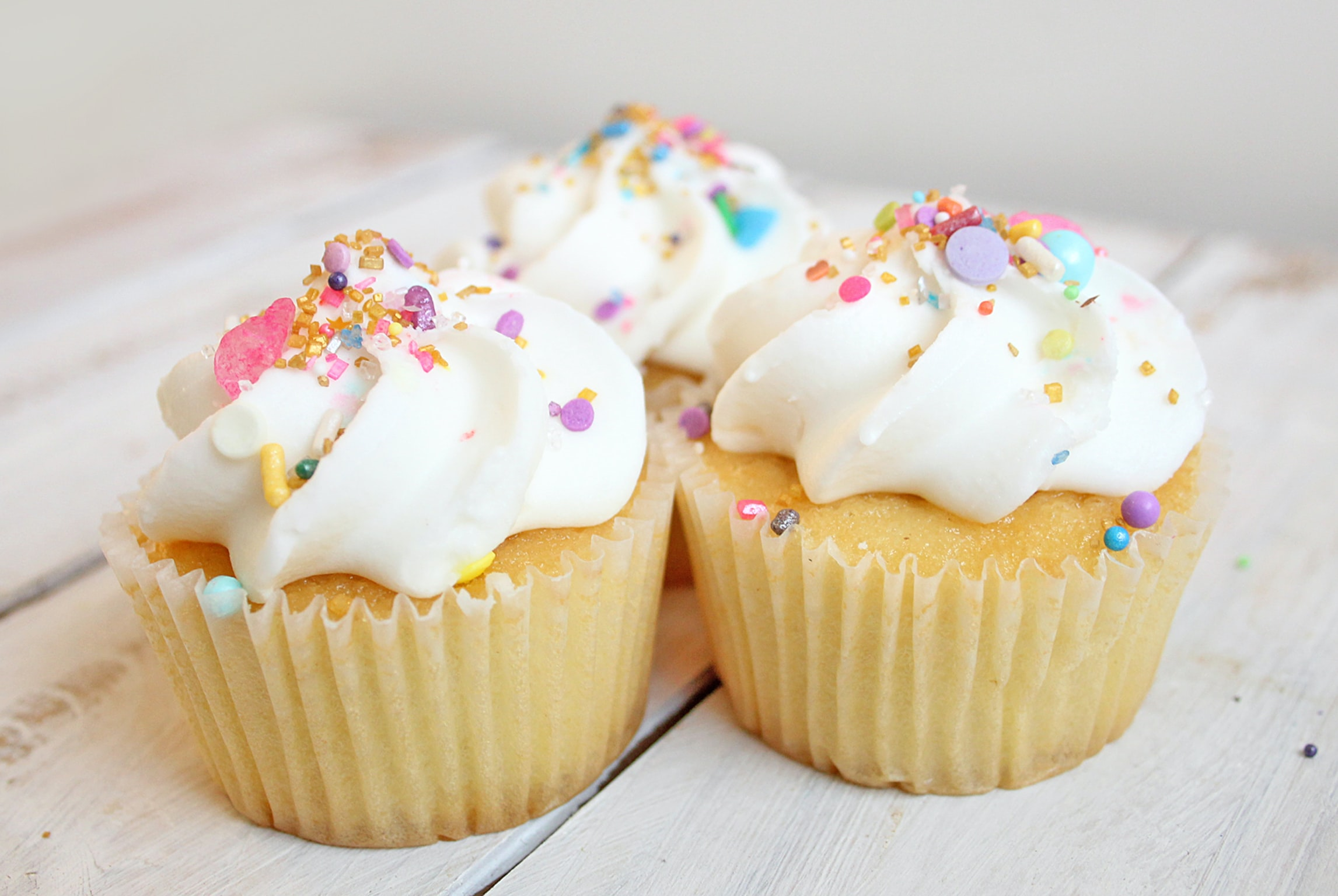 Three vanilla cupcakes with white frosting and sprinkles sit on a wooden surface.