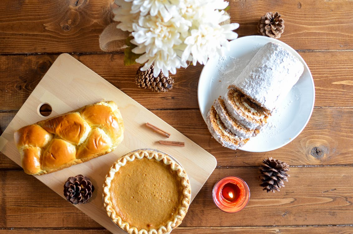 A pie, a loaf of bread, and a powdered loaf are displayed on a wooden counter with white flowers and pine cones.
