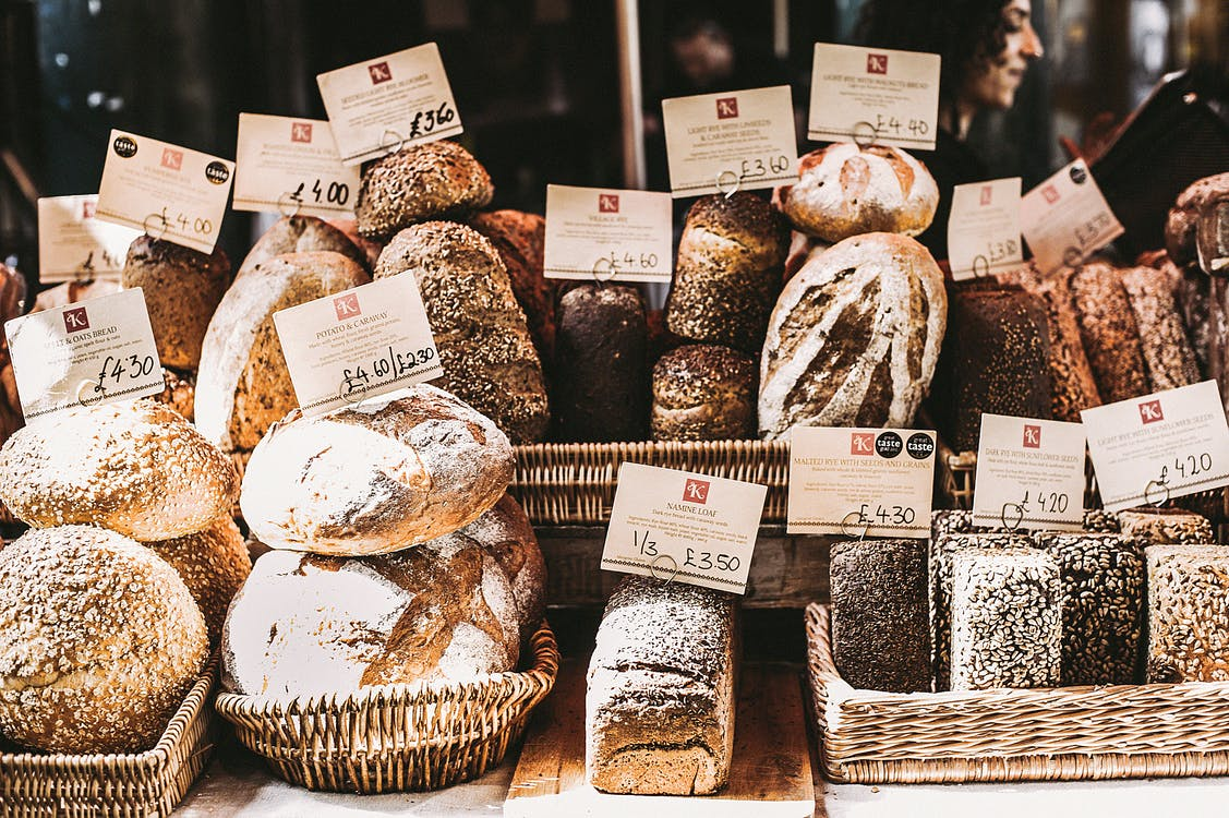 Several different breads are situated n display in baskets.