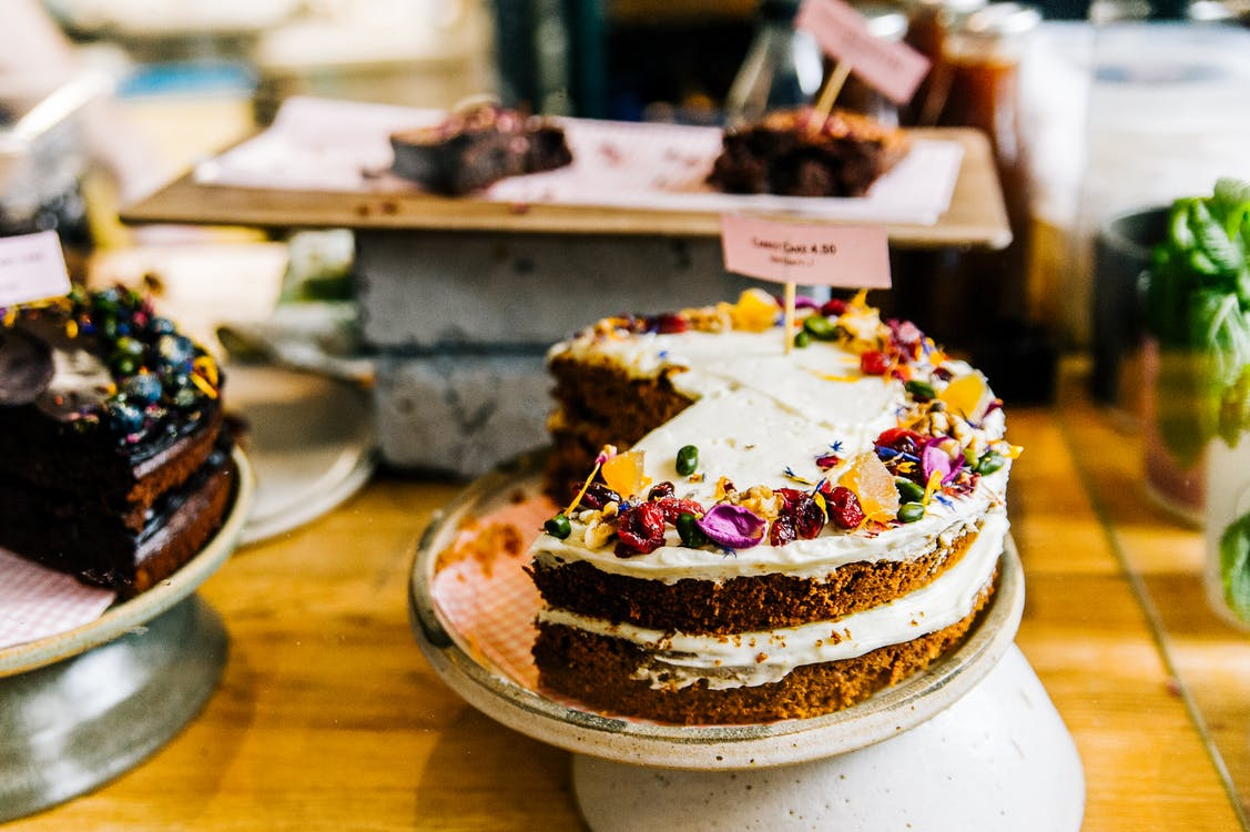 A layered cake is on display amongst other baked goods.