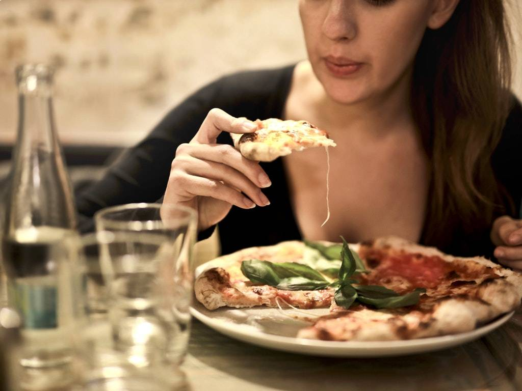 woman eating pizza at a restaurant