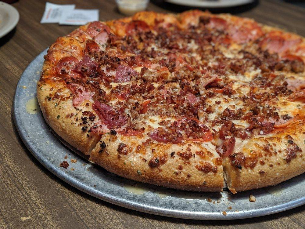 pizza with sausage, bacon, pepperoni, and ham