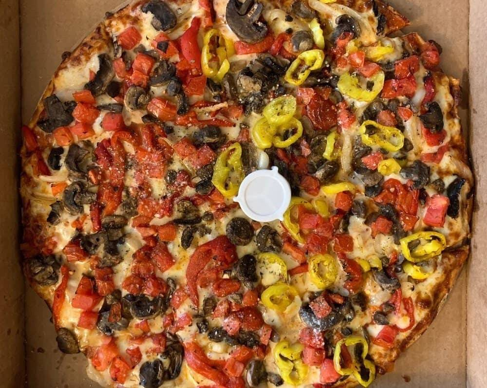 Pizza half shrooms and tomatoes half banana peppers