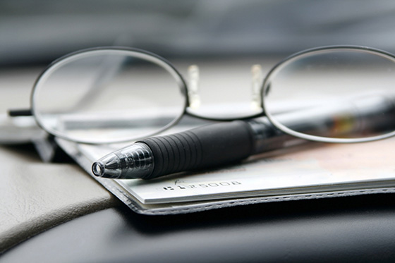 checkbook, pen and eyeglasses
