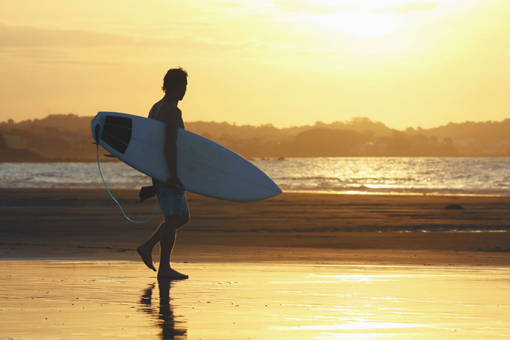 A surfer walks towards the water in the afternoon sun
