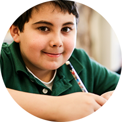 Boy smiling while doing classwork