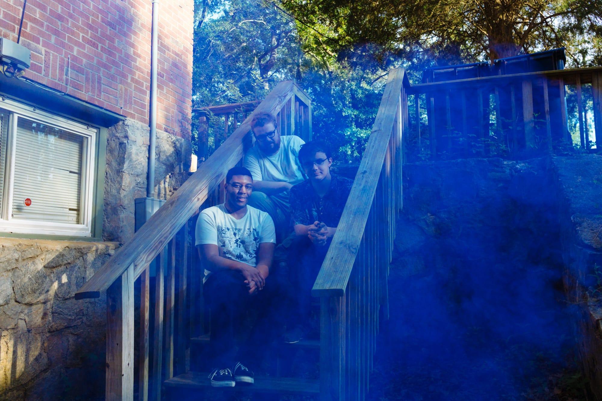 portrait of atlanta band Feverest with blue smoke