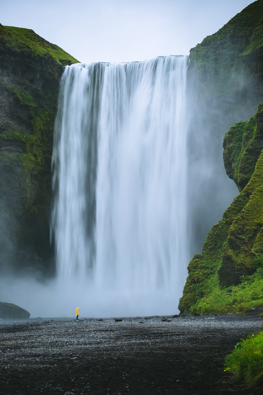 person standing next to waterfall