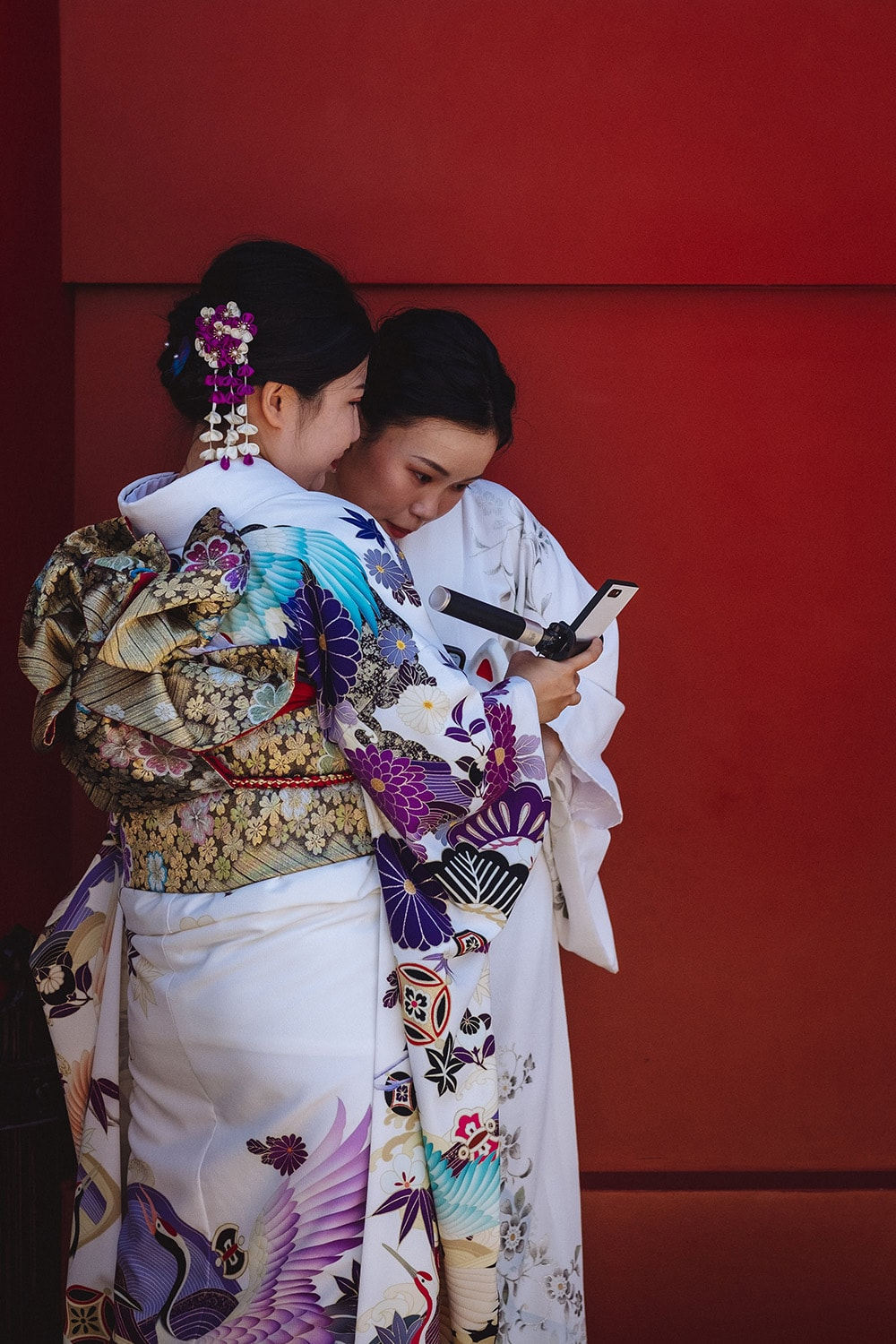 women wearing kimonos looking at phone