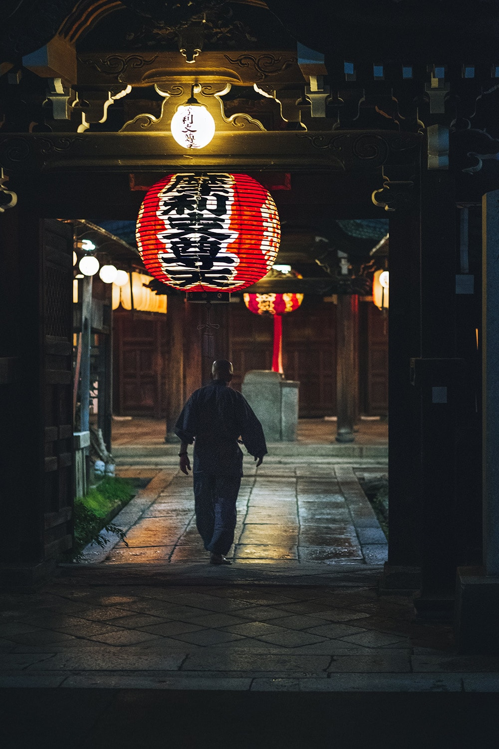 man walking into temple in Kyoto at night