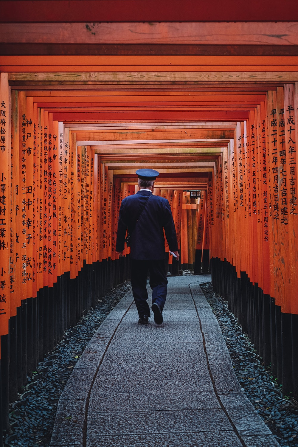man walking under torii gates in Kyoto